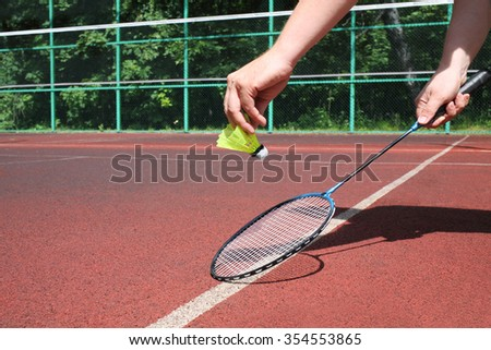 Male hands holding a badminton racket and shuttlecock on the tennis court - stock photo