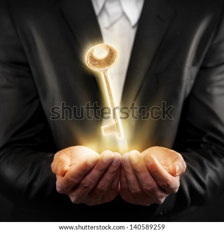 Male hands holding a golden key - stock photo