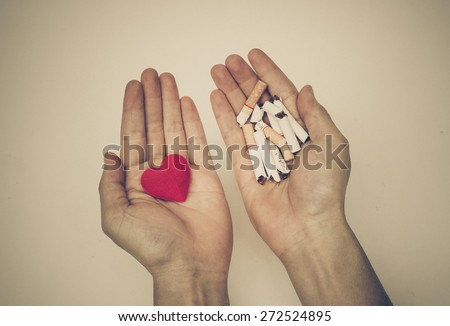 Male hands holding a red heart and broken cigarettes - Making a decision to stop smoking concept  - stock photo
