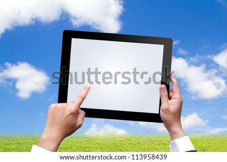 male hands holding a tablet on blue sky - stock photo