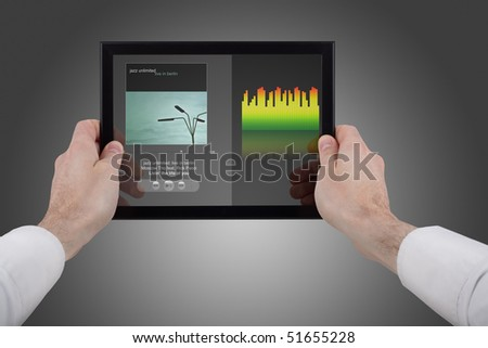 male hands holding a touchpad pc, using the music programme - stock photo