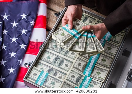 Male hands holding dollar bundles. Hands, money and american flag. Wealth and power. Income of successful politician. - stock photo