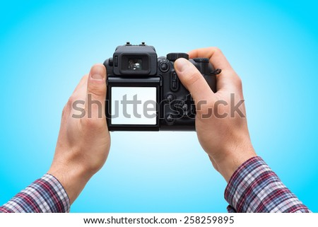 Male hands holding DSLR camera isolated on blue gradient background - In this photo the logos, brand, or anything that can bring to a particular object has been deleted to be 100% commercial.  - stock photo