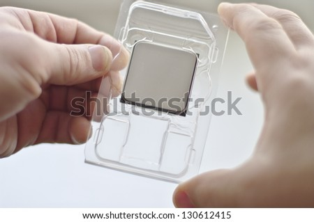 Male hands holding dual core CPU, central processing unit, microporcessor - stock photo