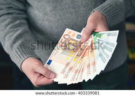 Male hands holding money in the form of a fan. Money, Euro currency (EUR) bills - stock photo