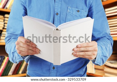 Male hands holding open book on bookshelves background - stock photo
