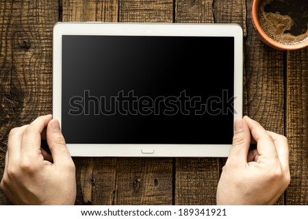 Male hands holding tablet pc with empty screen on wooden background - stock photo