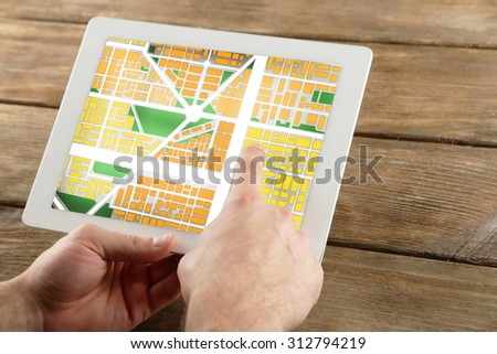 Male hands holding tablet pc with map gps navigation application on wooden table