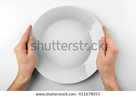 Male hands holding white plate, isolated on white - stock photo