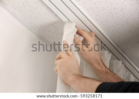 Male Hands Installing Curtains Over Window