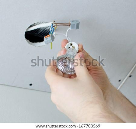 Male hands installing socket for light bulb - stock photo