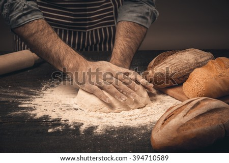 Male hands knead the dough. - stock photo
