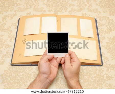 male hands on an old vintage photo album - stock photo