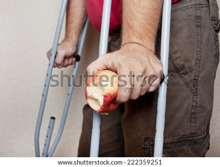 Male hands on crutches with an apple on wall background.