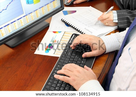 Male Hands on the Keyboard and Financial Data and Charts in the Office - stock photo