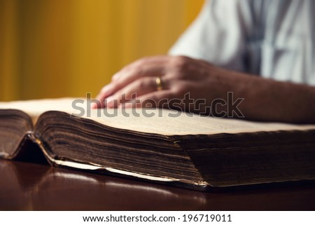 Male hands on 150 year old Bible - stock photo