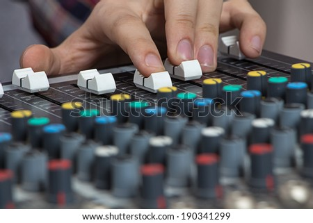 Male Hands operating small Sound console on the table - stock photo