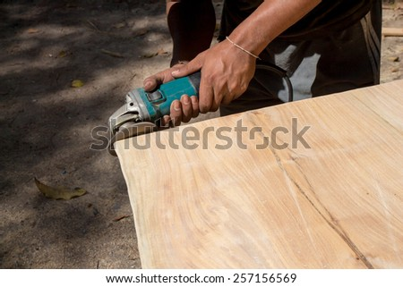 Male hands polishing wooden plank with polishing tools - stock photo