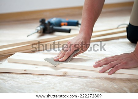 Male hands polishing wooden plank with sandpaper - stock photo