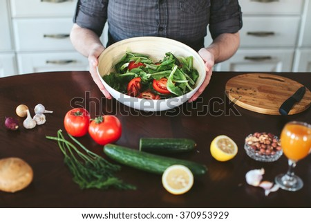 male hands preparing vegetarian salad in the kitchen - stock photo