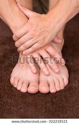 Male hands protecting clean and healthy pair of feet. - stock photo