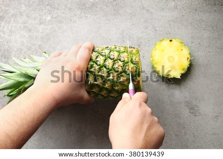 Male hands slicing pineapple.Top view - stock photo