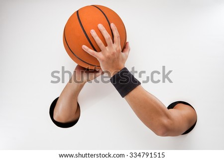 Male  hands through the holes on a white background are holding the basket ball before throwing - stock photo