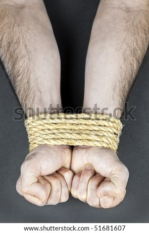 Male hands tied up with strong rope - stock photo