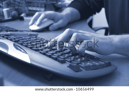 Male hands typing on keyboard, blue toned