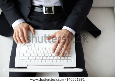 Male hands typing on laptop - stock photo
