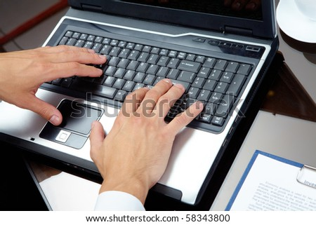 Male hands typing on the laptop