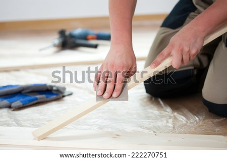 Male hands using sandpaper for polishing wooden plank - stock photo