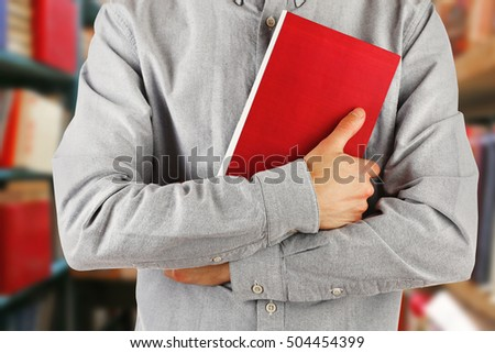 Male hands with book, closeup. School library concept.