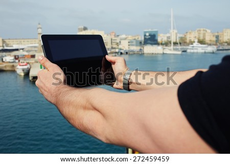 Male hands with digital tablet camera taking picture of beautiful city from viewpoint, male tourist photographing marina port city with touch pad, vacation holidays memories - stock photo