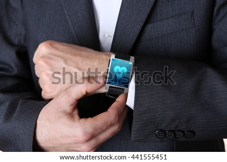 Male hands with heart icon on smart watch