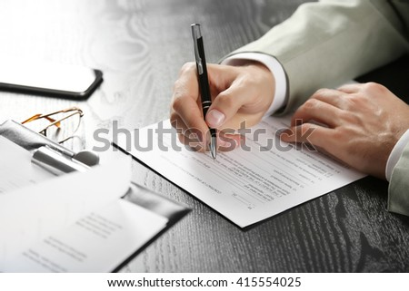 Male hands with pen signing document at the desk closeup