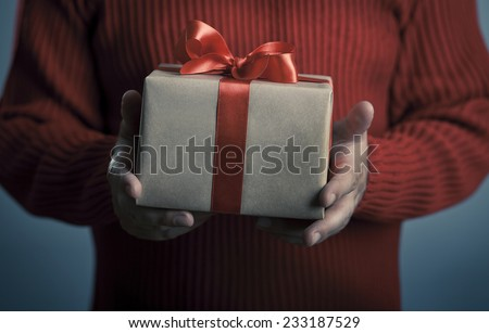 Male hands with red bow gift box. Valentine's or christmas concept. - stock photo