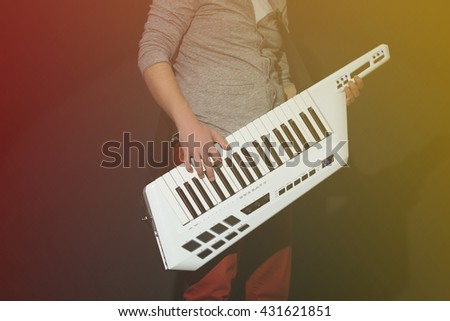 Male hands with synthesizer on dark background - stock photo