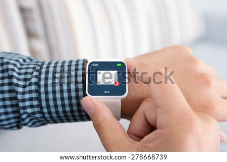 male hands with white smartwatch and email on the screen in the room - stock photo