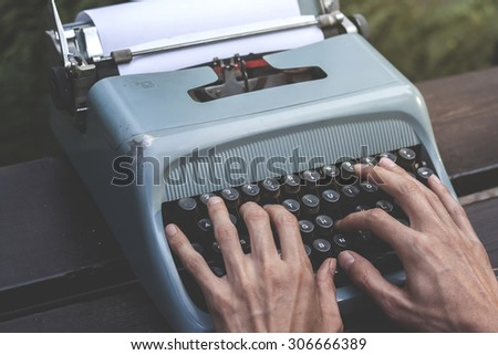 male hands writing with an old blue typewriter, vintage stock photo - stock photo