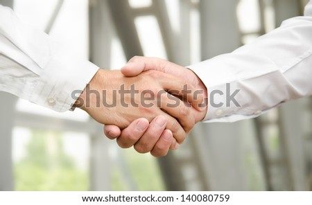Male handshake isolated on business background