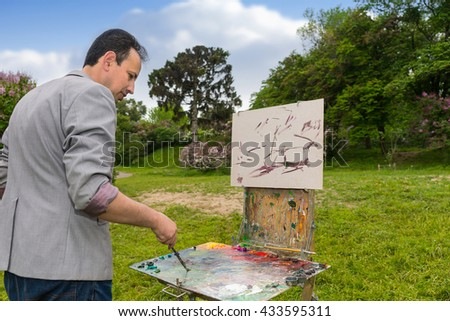 Male handsome artist mixing paint on a palette during creation a sketch  of his picture on a trestle and easel painting with oils and acrylics in a garden - stock photo