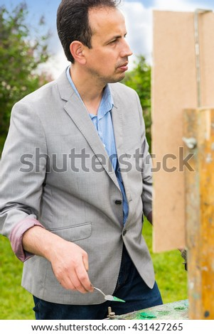 Male handsome middle-aged creative artist working  on a trestle and easel painting with oils and acrylics during an art class in a park - stock photo