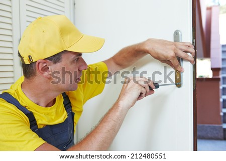 Male handyman carpenter worker at interior wood door lock installation or repairing - stock photo