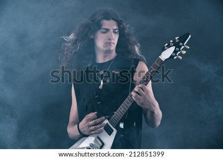 Male hard rock electric guitar musician with long hair. Studio shot against grey. - stock photo