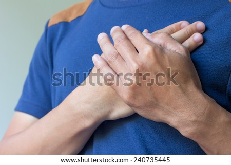 male having pain in his chest - stock photo