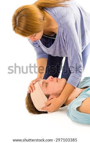Male head with bandage and drowsy eyes lying down while female hands holding. - stock photo