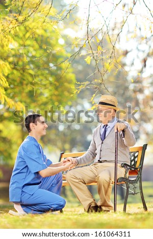Male healthcare professional helping senior man sitting on a wooden bench in a yard - stock photo