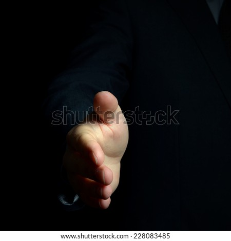 male helping hand from darkness or fake help, selective focus  - stock photo