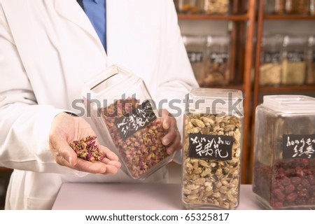 Male herbalist doctor with Chinese medicinal herbs - stock photo